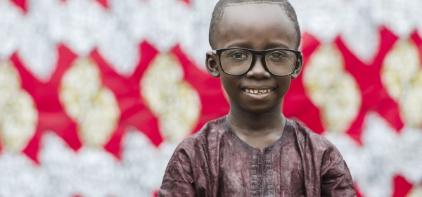 Image of a African child wearing glasses as part of article on Health Reform in the United States.